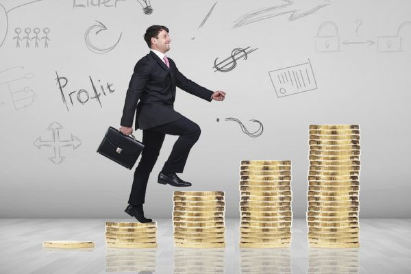 Businessman climbing gold coins stacks on the gray background